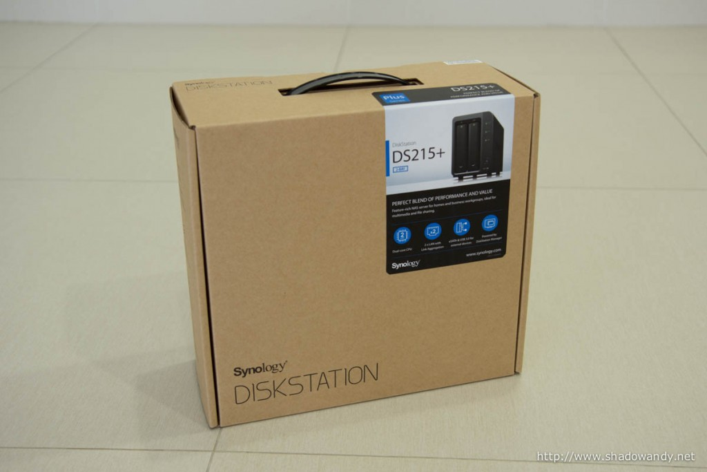 """The Synology DS215+ in its usual brown """"carton box"""" packaging."""