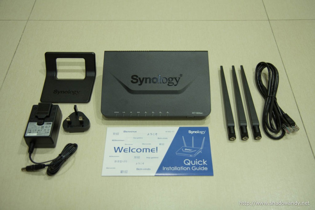 The Synology RT1900ac laid out: RT1900ac WiFi router, stand attachment, power adaptor, dual-band antennas, ethernet patch cord and quick installation guide.